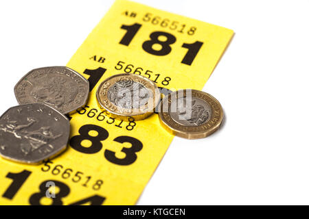 strip of yellow raffle tickets with uk coins stock photo