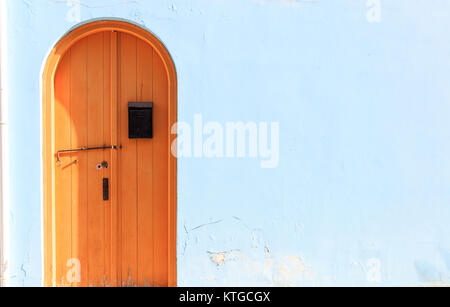 Brown wooden door on light blue backdrop. Closeup view, space for text - Stock Photo