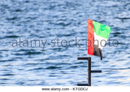 View of the UAE Flag from Al Seef Area in Old Dubai. - Stock Photo
