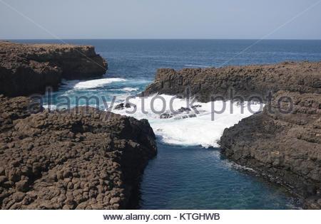 Progressing wave in ocean tide pool, Buracona, Cape Verde - Stock Photo