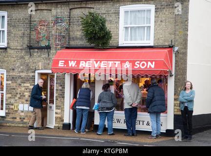 People queue outside E W Revett and Son butcher shop, Wickham Market, Suffolk, England, UK - Stock Photo