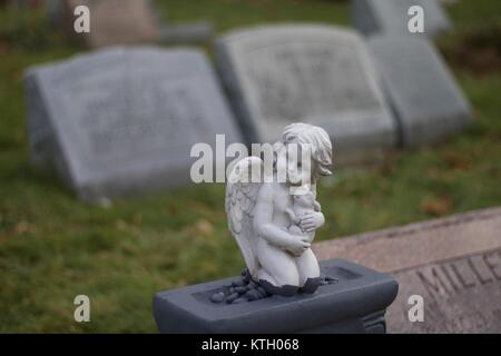 Exterior daytime shallow depth of field stock photo of cherub angel atop headstone in Mt. Hope Cemetary in Rochester, - Stock Photo