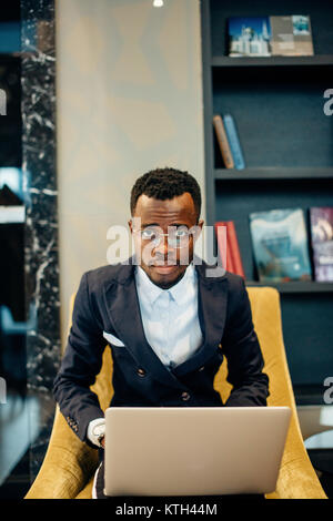 Employee wearing suit working online on laptop - Stock Photo