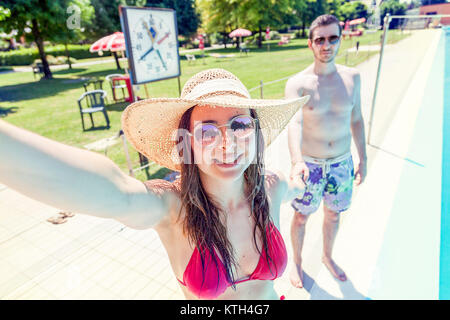 Young loving couple beside the pool takes a selfie in swimsuit. Concept of young people having fun in summertime - Stock Photo