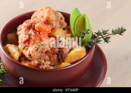 Braised  meat with potatoes and carrots in a ceramic pot. - Stock Photo