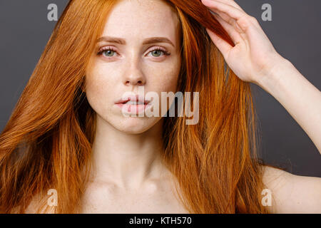redhead woman holding her healthy and shiny hair, studio grey - Stock Photo