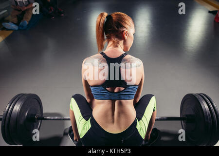 Rear view of sportswoman while lifting barbell - Stock Photo