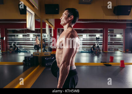 muscular man doing squats exercise with barbell - Stock Photo