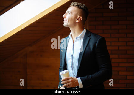handsome businessman drinking coffee in home and looking away - Stock Photo
