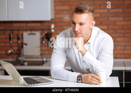 man working at home on some project, sitting at white table looking at laptop - Stock Photo