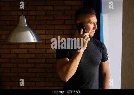 man talking on phone in home near window - Stock Photo