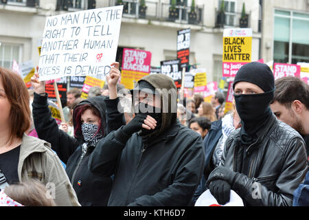 """UN Anti-Racism Day: Anti-racism anti-fascist protester carries a placard: """"No man has the right to tell another - Stock Photo"""