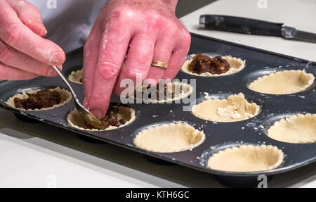 Close up of man's hands with wedding ring filling mince pie cases with mincemeat ready for baking on a white kitchen - Stock Photo