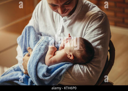 Father With Newborn Baby Working From Home Using Laptop - Stock Photo