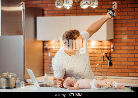 father are spending time with baby. Dad is doing selfie using a smartphone - Stock Photo
