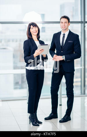 two businessmen using touchpad at meeting - Stock Photo