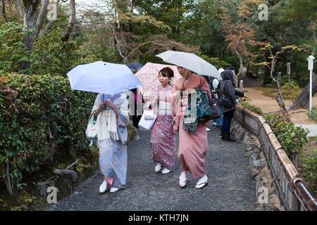 JAPAN, KYOTO-CIRCA APR, 2013: Three geishas wearing traditional japanese kimono are on pathway in Kinkaku-ji temple - Stock Photo