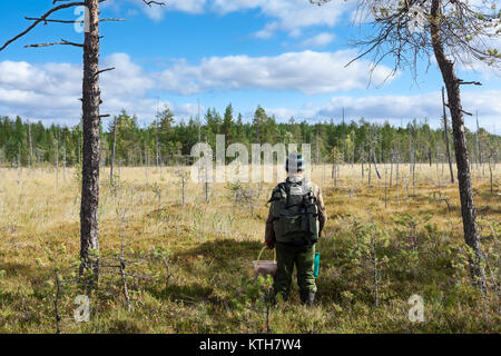 Man with backpack and bucket standing in front of wet swamp, lost in woods - Stock Photo