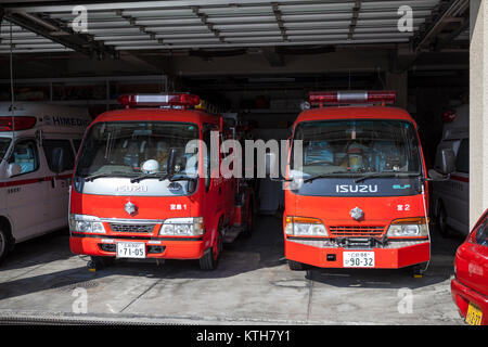 ITSUKUSHIMA, JAPAN-CIRCA APR, 2013: Two small fire-fighter trucks stand in garage with opened gates. Japanese fire - Stock Photo