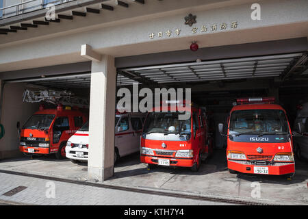 ITSUKUSHIMA, JAPAN-CIRCA APR, 2013: Fire-fighter and ambulance cars stand in garage with opened gates. Japanese - Stock Photo