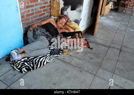 A homeless woman lying on a sidewalk in a street in Los Angeles, California USA  KATHY DEWITT - Stock Photo