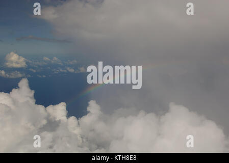 Rainbow in the clouds while a flight over the Indian Ocean - Stock Photo