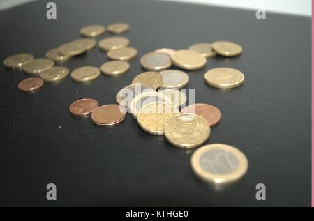 some euro coins and pennies on a dark background giving people the idea of money saving in bad economical situations.take - Stock Photo