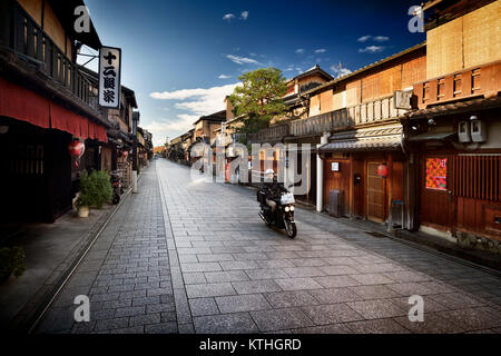 Motorcyclist on an empty Hanamikoji Dori street in Gion district in morning sunrise before all the shops and restaurants - Stock Photo