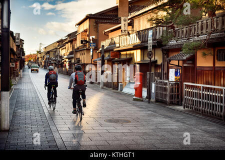 Cyclists on an empty Hanamikoji Dori street in Gion district in morning sunrise before all the shops and restaurants - Stock Photo
