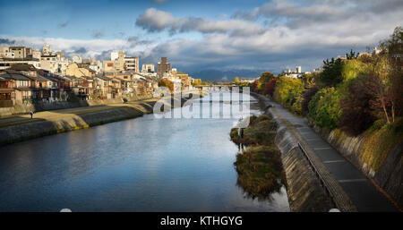 Kamo River, Kamo-gawa, with pathways along the banks and people fishing. Kyoto beautiful panoramic sunrise scenery - Stock Photo