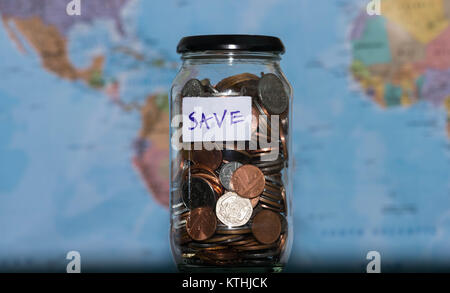 Travel budget concept. Money saved for vacation in glass jar on world map background, copy space. coins for big - Stock Photo