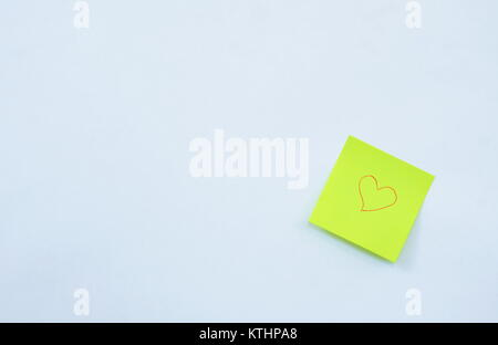yellow paper note drawing red heart shape stick on white background - Stock Photo