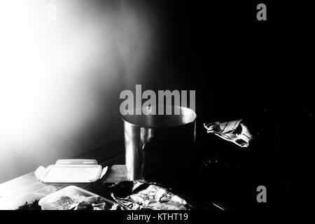 Cooking water coming from a pot making a lot of steam in a freezing room within a unmanned chalet in the Swiss Alps - Stock Photo