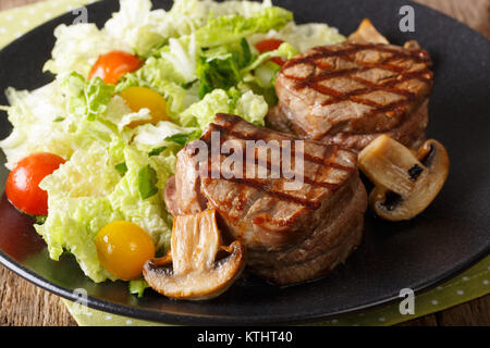 Delicious filet minion steak with fresh vegetable salad and mushrooms close-up on a plate. horizontal - Stock Photo