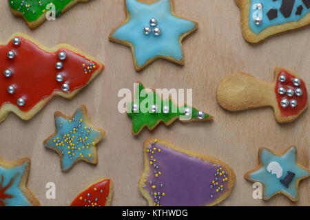 Pastel colored cookies with silver pearls on a bright wooden background - Stock Photo
