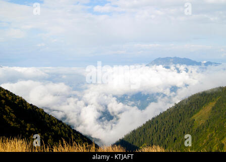 morning view of the Achishkho mountain in the Caucasus from the pass Bzerpinsky cornice, towering above the clouds - Stock Photo