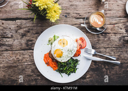 Breakfast with fried eggs, salmon, avocado, baked tomato, toast and greens. Cup of aroma cappuccino on wooden textured - Stock Photo