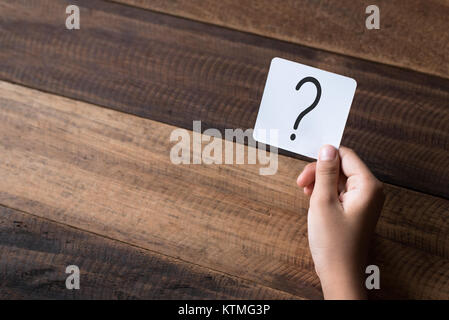 hand holding a note written a question mark on a wooden table background - Stock Photo