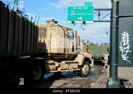 MANHATTAN, NY – 53rd Troop Command guardsman directing convoy parking along 12th Avenue. Army Guard transport vehicles - Stock Photo