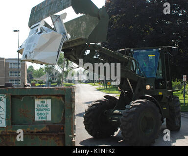 MOHAWK, NY –New York Army National Guard Soldier Sgt. John Johnson uses a front-end loader to drop flood-damaged - Stock Photo