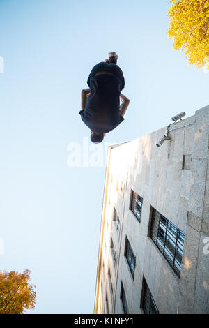 Young man doing a side flip or somersault while practicing parkour on the street. - Stock Photo