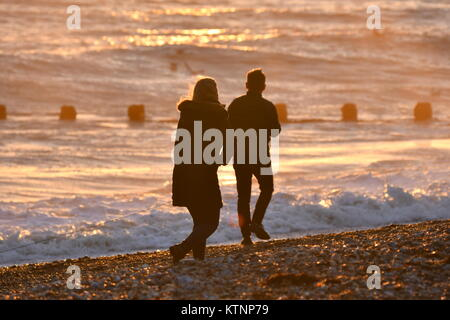 Young couple silhouettes walking arm in arm along the beach by the sea on a Winter evening in the UK. - Stock Photo