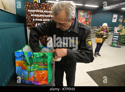 St Petersburg, Russia. 28th Dec, 2017. A security guard examines a customer's bag outside a Perekrestok supermarket. - Stock Photo