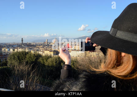 View from behind of a young girl with a hat that takes a picture to the Florence panorama seen from the piazzale - Stock Photo