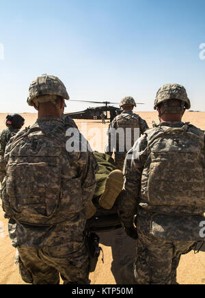Medics from 1st Battalion, 67th Armor Regiment, 2nd Armored Brigade Combat Team, 4th Infantry Division, carry Pfc. - Stock Photo