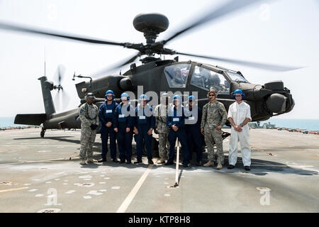 The deck crew of the RFA Cardigan Bay, Royal Fleet Auxiliary, U.K. Royal Navy, stand in front of an AH-64 Apache - Stock Photo