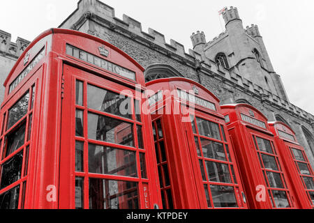 Cambridge, England - 04 29 2017: A row of four classic K6 red phone boxes standing aside Great St. Mary's Church, - Stock Photo