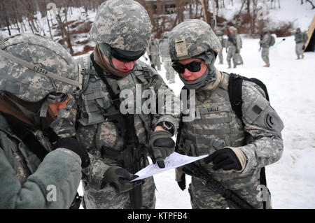 Sgt. Ronnie Cocha (left), Cpt. Bryan Hoffman and 1st Lt. Yvette Valle start to plot out points on the map they were - Stock Photo