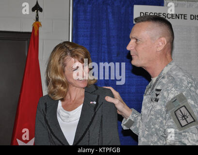 Jennifer MacPhee, managing director of the Merrill Lynch office in Albany, is congratulated by Major General Patrick - Stock Photo