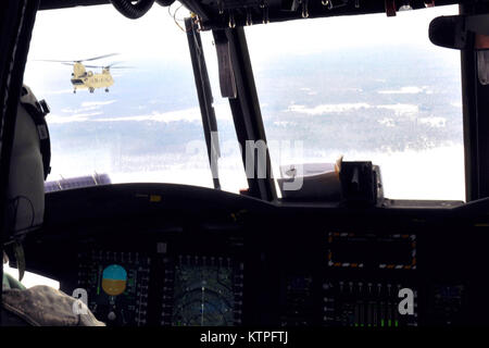 Pilots of a New York Army National Guard CH-47F helicopter assigned to  Company B 3rd Battalion 126th Aviation watch - Stock Photo